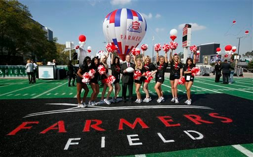 In this Feb. 1, 2011, file photo, Paul Patsis, president of Market Management for Farmers Insurance, center, poses with Los Angeles Kings cheerleaders during a ceremony naming a new proposed NFL football stadium in Los Angeles.