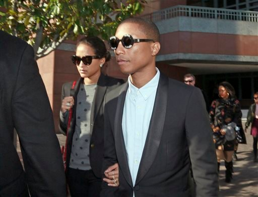 In this Wednesday, March 4, 2015 photo, Pharrell Williams and an unidentified woman leave Los Angeles Federal Court after testifying at trial in Los Angeles.