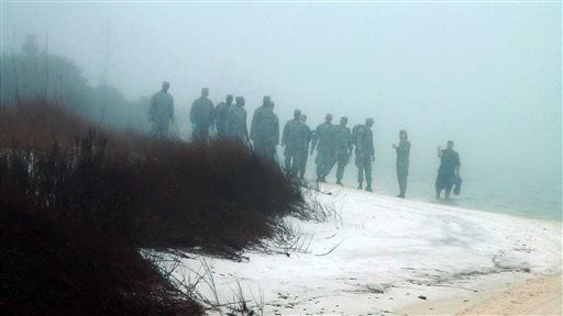 Military personnel wade in the water and search on the beach under heavy fog at Eglin Air Force Base, Fla., Wednesday, March 11, 2015, for the wreckage of a military helicopter that crashed with 11 service members aboard. (AP)