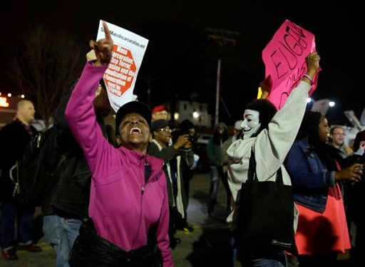 People demonstrate across the street from the Ferguson Police Department, Thursday, March 12, 2015, in Ferguson, Mo. Two police officers were shot early Thursday morning in front of the Ferguson Police Department during a protest following the resignation