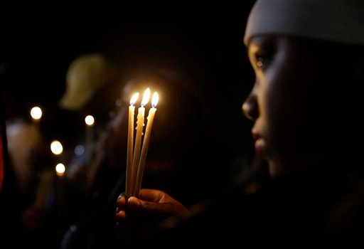 Chaunte Williams, 13, holds up three candles as she takes part in a vigil Thursday, March 12, 2015, in Ferguson, Mo. Two police officers were shot early Thursday morning in front of the Ferguson Police Department during a protest following the resignation