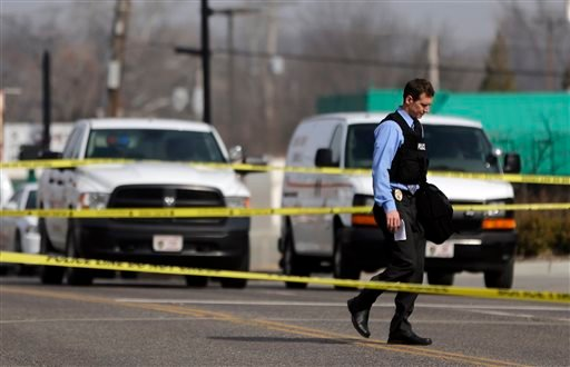 A police officer walks toward the Ferguson Police Department Thursday, March 12, 2015, in Ferguson, Mo. Two officers were shot in front of the police department early Thursday as demonstrators gathered after the police chief resigned in the wake of a scat