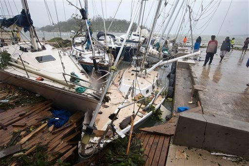 In this image provided by UNICEF Pacific, people on a dock view yachts damaged in Port Vila, Vanuatu, Saturday, March 14, 2015, in the aftermath of Cyclone Pam. Winds from the extremely powerful cyclone that blew through the Pacific's Vanuatu archipelago