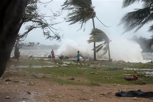 In this image provided by UNICEF Pacific people walk along the shore where debris is scattered in Port Vila, Vanuatu, Saturday, March 14, 2015, in the aftermath of Cyclone Pam. Winds from the extremely powerful cyclone that blew through the Pacific's Vanu