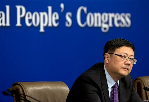 In this March 7, 2015 photo, China's Environment Minister Chen Jining listens to a reporter's question during a press conference in Beijing. Since China launched a sweeping legal reform in January that toughens environmental penalties and allows more grou