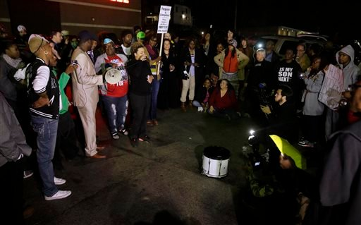 Protesters gather across the street from the Ferguson Police Department, Thursday, March 12, 2015, in Ferguson, Mo. Two police officers were shot early Thursday morning in front of the Ferguson Police Department during a protest following the resignation