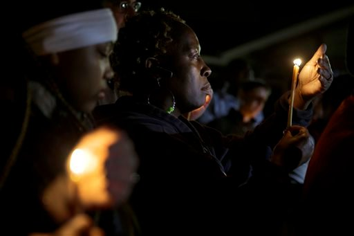 People take part in a candlelight vigil Thursday, March 12, 2015, in Ferguson, Mo. Two police officers were shot early Thursday morning in front of the Ferguson Police Department during a protest following the resignation of the city's police chief in the