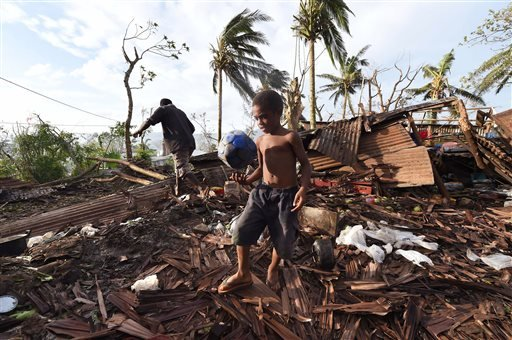 Samuel, only his first name given, carries a ball through the ruins of their family home as his father, Phillip, at back, picks through the debris in Port Vila, Vanuatu in the aftermath of Cyclone Pam Monday, March 16, 2015. Vanuatu's President Baldwin Lo