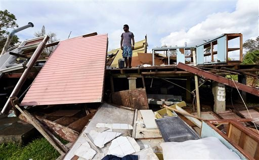 Adrian Banga surveys his destroyed house in Port Vila, Vanuatu in the aftermath of Cyclone Pam, Monday, March 16, 2015. Vanuatu's President Baldwin Lonsdale said Monday that the cyclone that hammered the tiny South Pacific archipelago over the weekend was