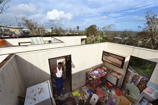 """Uwen Garae surveys his damaged house in Port Vila, Vanuatu in the aftermath of Cyclone Pam Monday, March 16, 2015. Vanuatu's President Baldwin Lonsdale said Monday that the cyclone that hammered the tiny South Pacific archipelago over the weekend was a """"m"""