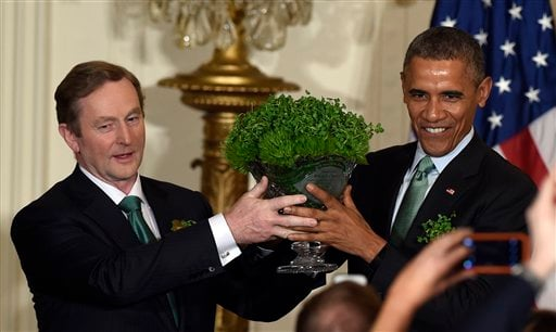 President Barack Obama, right, and Irish Prime Minister Enda Kenny, left, hold up a bowl of shamrocks during a reception in the East Room of the White House in Washington, Tuesday, March 17, 2015. (AP)