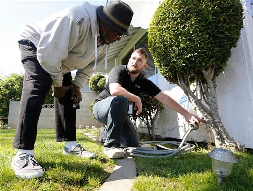FILE -- In this March 11, 2014 file photo Steve Upton, right, demonstrates how to use the water timer he installed on the water spigot at the home of Larry Barber, left, in Sacramento, Calif. (AP)