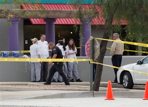 Mesa police talk to eyewitness at the scene of a shooting, Wednesday, March 18, 2015 in Mesa, Ariz. (AP Photo/The Arizona Republic, Nick Oza)
