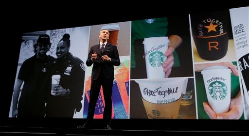 Starbucks CEO Howard Schultz speaks while photos of coffee cups with #RaceTogether written on them are projected behind him, Wednesday, March 18, 2015, at the coffee company's annual shareholders meeting in Seattle. (AP)