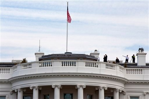 Uniformed Secret Service agents patrol the top of the White House as seen from the South Lawn of the White House in Washington, Tuesday, March 17, 2015. (AP)