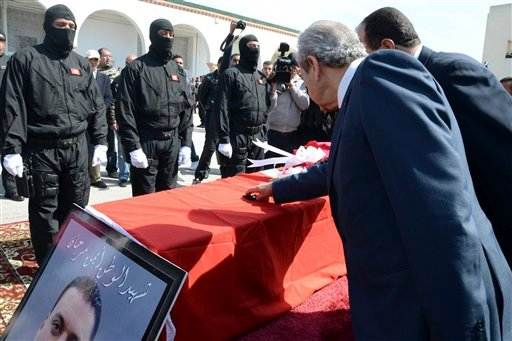 Hooded police officers stand while Tunisian Interior Minister Mohamed Najem Gharsalli, right, and House Speaker Mohamed Ennaceur, second right, touch the coffin of elite security member Aymen Morjen, Thursday March 19, 2015. (AP)