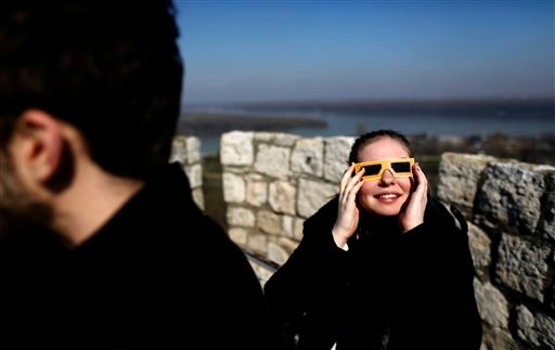 A girl watches the solar eclipse through goggles at Kalemegdan citadel in Belgrade, Serbia, Friday, March 20, 2015. Clouds moving over the city allowed only brief views of the eclipse which in southern Europe was partial. (AP Photo/Darko Vojinovic)