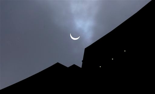 The moon blocks part of the sun during a partial eclipse over Brussels, Belgium on Friday, March 20, 2015. (AP Photo/Virginia Mayo)