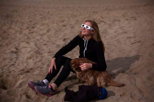 Victoria, from Birmingham, looks up to the sun wearing protective goggles as she sits on the beach with her dog during a partial solar eclipse in Barcelona, Spain, Friday, March 20, 2015. (AP Photo/Emilio Morenatti)