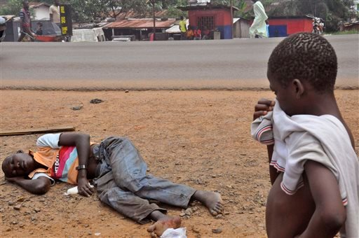 In this Friday, Sept. 12, 2014 file photo, a child covers his face as he looks at a man suspected of suffering from the Ebola virus, in a main street and busy area of Monrovia, Liberia. In a delay that some say may have cost lives, the World Health Organi