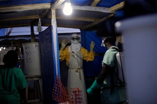 In this Thursday, Nov. 20, 2014 file photo, a Medecins sans Frontieres (Doctors without Borders) Ebola heath worker is sprayed as he leaves the contaminated zone at the Ebola treatment centre in Gueckedou, Guinea. In a delay that some say may have cost l