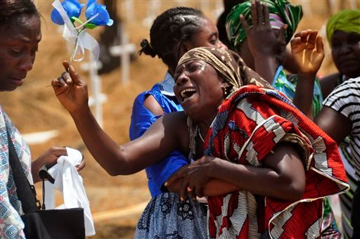 In this Wednesday, March 11, 2015 file photo, relatives weep as they bury a loved one suspected of dying from the Ebola virus at a new graveyard on the outskirts of Monrovia, Liberia. In a delay that some say may have cost lives, the World Health Organiza