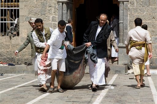 Yemenis carry a body of a man killed in a bomb attack at a mosque in Sanaa, Yemen, Friday, March 20, 2015. Triple suicide bombers hit a pair of mosques crowded with worshippers in the Yemeni capital, Sanaa, on Friday, causing heavy casualties, according t