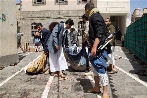 Houthi fighters carry a body of a man killed in a suicide attack that struck a mosque in Sanaa, Yemen, Friday, March 20, 2015. Triple suicide bombers hit a pair of mosques crowded with worshippers in the Yemeni capital, causing heavy casualties, according