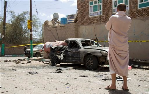 A man looks at a damaged car after a suicide attack in Sanaa, Yemen, Friday, March 20, 2015. Triple suicide bombers hit a pair of mosques crowded with worshippers in the Yemeni capital, Sanaa, on Friday, causing heavy casualties, according to witnesses. T