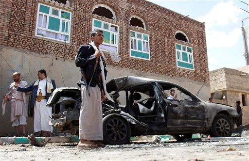 Houthi fighters stand near a damaged car after suicide attack in Sanaa, Yemen, Friday, March 20, 2015. Triple suicide bombers hit a pair of mosques crowded with worshippers in the Yemeni capital, Sanaa, on Friday, causing heavy casualties, according to wi