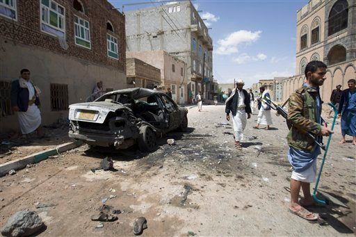 Shiite rebels, known as Houthis, stand near a damaged car after a bomb attack in Sanaa, Yemen, Friday, March 20, 2015. Triple suicide bombers hit a pair of mosques crowded with worshippers in the Yemeni capital, Sanaa, on Friday, causing heavy casualties,