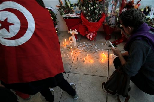 Women set up candles during a demonstration in front of the National Bardo Museum a day after gunmen attacked the museum and killed scores of people in Tunis, Tunisia, Thursday, March 19, 2015. The Islamic State group issued a statement Thursday claiming