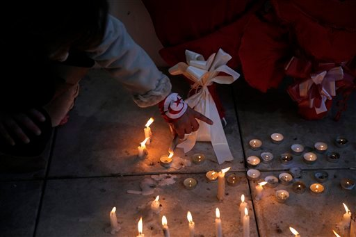 A woman sets up candles during a demonstration in front of the National Bardo Museum a day after gunmen attacked the museum and killed scores of people in Tunis, Tunisia, Thursday, March 19, 2015. The Islamic State group issued a statement Thursday claimi