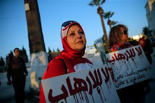 "A woman holds a placard reading: ""No to Terrorism"" as she demonstrates in front of the National Bardo Museum a day after gunmen attacked the museum and killed scores of people in Tunis, Tunisia, Thursday, March 19, 2015. The Islamic State group issued a s"