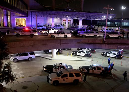Dozens of police vehicles surround the entrance to New Orleans Louis Armstrong International Airport after a machete-wielding man was shot by a TSA employee in Concourse B on Friday, March 20, 2015. (AP Photo/NOLA.com The Times-Picayune, Michael DeMocker,