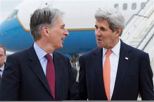 U.S. Secretary of State John Kerry, right, is greeted by British Foreign Secretary Philip Hammond in London, England, Saturday, March 21, 2015, for a meeting about the recently concluded round of negotiations with Iran over Iran's nuclear program. (AP Pho