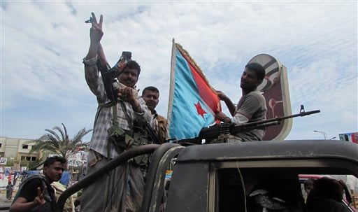 In this photo taken on Friday, March 20, 2015, militiamen loyal to President Abed Rabbo Mansour Hadi ride on an army vehicle on a street in Aden, Yemen. One of them holds a representation of the old South Yemen flag that was used when southern Yemen was a