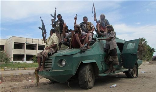 In this photo taken on Friday, March 20, 2015, militiamen loyal to President Abed Rabbo Mansour Hadi ride on an army vehicle on a street in Aden, Yemen. The country's Shiite rebels issued a call to arms Saturday to battle forces loyal to the embattled Pre