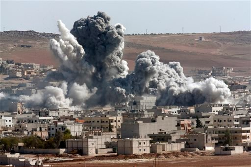 In this Oct. 22, 2014, file photo, thick smoke from an airstrike by the US-led coalition rises in Kobani, Syria, as seen from a hilltop on the outskirts of Suruc, at the Turkey-Syria border. (AP Photo/Lefteris Pitarakis, File)
