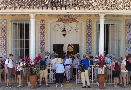 In this Feb. 25, 2015 photo, tourists look for souvenirs at a shop in Trinidad, southern Cuba. (AP Photo/Enric Martí)