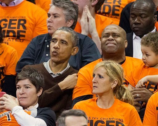 President Barack Obama, left, with his brother-in-law Craig Robinson, right, react to to Wisconsin-Green Bay scoring against Princeton during the second half of a women's college basketball game.