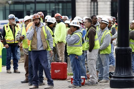 Construction workers gather outside the scene where a section of scaffolding collapsed at a high-rise construction project, killing three people and sending another to a hospital, Monday, March 23, 2015, in downtown Raleigh, N.C. (AP Photo/The News & Obse