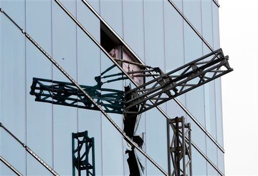 A section of scaffolding protrudes from a shattered window at the scene of a construction accident that killed three people and sent another to a hospital, Monday, March 23, 2015, in Raleigh, N.C. A scaffolding holding at least three workers fell and cras