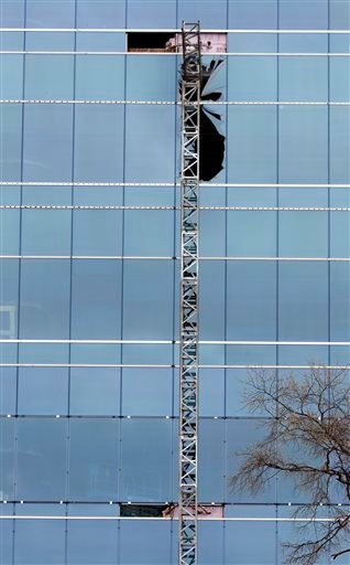 A section of scaffolding framework hangs from the side of the Charter Square building at the scene of a construction accident in downtown Raleigh, NC that killed three people and sent another to a hospital, Monday, March 23, 2015. A scaffolding holding at