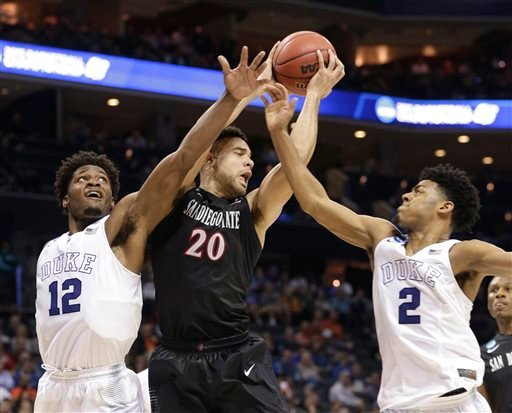 San Diego State's J.J. O'Brien (20) is trapped by Duke's Justise Winslow (12) and Quinn Cook (2) during the first half of an NCAA tournament college basketball game in the Round of 32 in Charlotte, N.C., Sunday, March 22, 2015. (AP Photo/Nell Redmond)