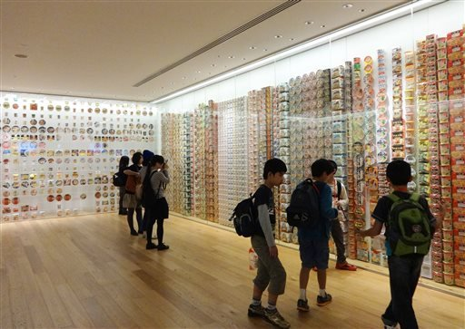 In this Oct. 17, 2014 photo provided by Linda Lombardi, visitors look at a variety of instant ramen soup packages on display at the Cup Noodle Museum in Yokohama, Japan.