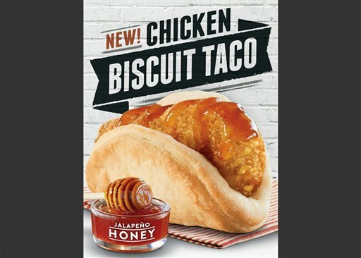 "This image provided by Taco Bell shows an ad shows the restaurant chain's new chicken ""biscuit taco""."