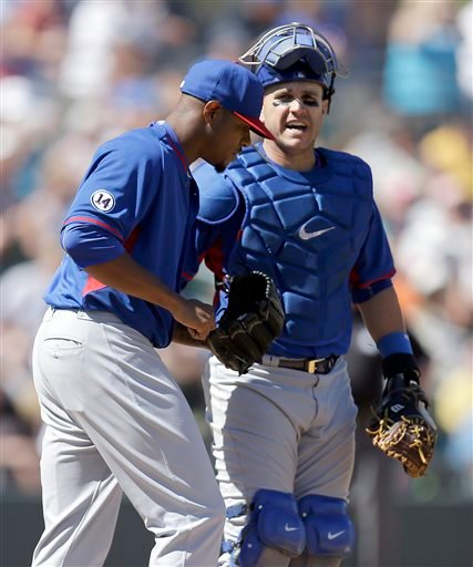 Chicago Cubs' Edwin Jackson, left, speaks with catcher Miguel Montero in the third inning of a spring training exhibition baseball game against the Oakland Athletics Tuesday, March 24, 2015, in Mesa, Ariz.