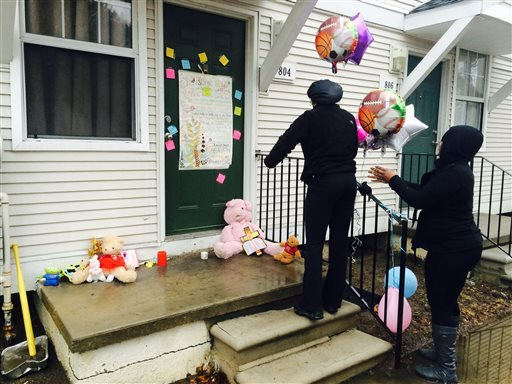 Toni Williams, 28, left, and Natasha Bell, 30, leave balloons at a town home in Detroit, Wednesday, March 25, 2015, where two bodies were found.