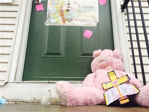 Teddy bears and notes are left at a town home in Detroit, Wednesday, March 25, 2015, where two bodies were found.
